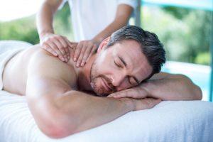 Man receiving back massage from masseur